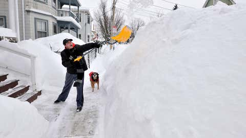 Lee Anderson adds to the pile of snow beside the sidewalk in front of his house in Somerville, Mass., Tuesday, Feb. 10, 2015, as his dog Ace looks on. (AP Photo/Josh Reynolds)