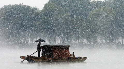 A man rows a boat on the West Lake in the snow on Dec. 5, 2015 in Hangzhou, Zhejiang Province of China. (ChinaFotoPress via Getty Images)