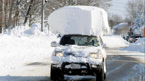 A vehicle, with a large chunk of snow on its top, drives along Route 20 after digging out after a massive snow fall in Lancaster, N.Y. Wednesday, Nov. 19, 2014. (AP Photo/Gary Wiepert)