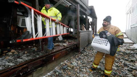 An unidentified town official helps Greg Longo, left, remove belongings from his house after it was heavily damaged by ocean waves during a winter storm in Marshfield, Mass., Tuesday, Jan. 27, 2015.  The storm has punched out a section of the seawall in the coastal town of Marshfield, police said. (AP Photo/Michael Dwyer)