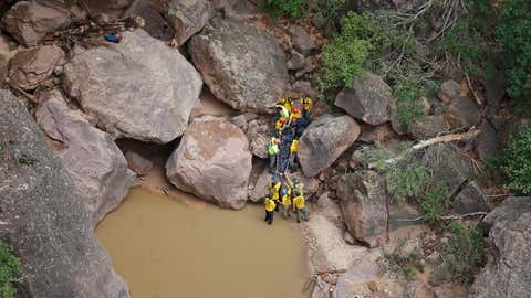 Search and rescue team members carry a body after it was found along Pine Creek, Wednesday, Sept. 16, 2015, in Zion National Park, near Springdale, Utah. Authorities are searching for other hikers killed in flash flooding that swept through a narrow canyon at Utah's Zion National Park. (AP Photo/Rick Bowmer)