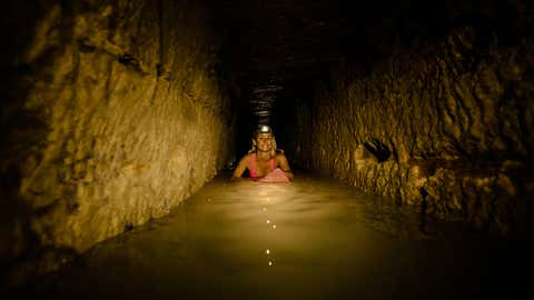 """Real-life """"Indiana Jane,"""" Alison Teal, 30, from Hawaii, took her bright pink board 492 feet underground to surf with over six million skeletons, becoming the first person known to """"surf"""" the world's largest grave. (Alex Voyer/Caters News)"""