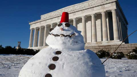 A snowman made with cookies and a red plastic cup sits in front of the Lincoln Memorial in Washington, Wednesday, Jan. 22, 2014. (AP Photo/Charles Dharapak)