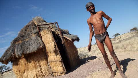 This photo taken on July 4, 2010 shows a bushman, known in the community as Gert, standing in front of a traditional bushveld toilet in Andries Vale village in the Kalahari, Northern Cape. (PABALLO THEKISO/AFP/Getty Images)