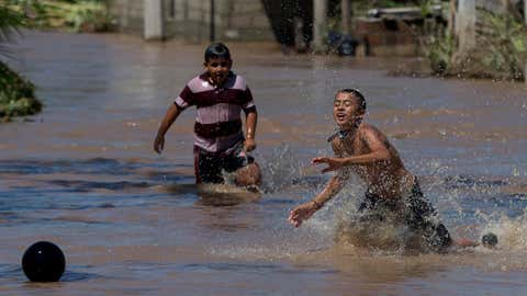 Boys play in the receding floodwaters two days after the passage of Hurricane Patricia in the village of Rebalse, Jalisco state, Mexico, Sunday, Oct. 25, 2015. (AP Photo/Rebecca Blackwell)