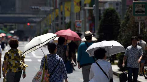 Pedestrians walk on the street under the sun at the Ginza shopping district in Tokyo on July 19, 2015. (Toshifumi Kitamura/AFP/Getty Images)