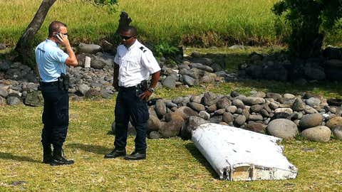 Officials stand next to a piece of debris from an unidentified aircraft found in the coastal area of Saint-Andre de la Reunion, in the east of the French Indian Ocean island of La Reunion, on July 29, 2015. (YANNICK PITOU/AFP/Getty Images)