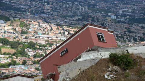 Collapsed houses in Ciudad del Angel, north from Tegucigalpa, on August 11, 2015. Built on geologically unstable hillsides, Ciudad del Angel has been declared unsuitable for occupation and will be demolished soon. So far 120 out of 250 houses built have already collapsed. (Orlando Sierra/AFP/Getty Images)
