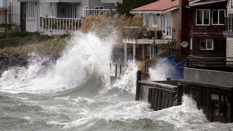 Wind-blown waves batter houses Tuesday, Nov. 17, 2015, in Seattle. Rain and high winds snarled the morning commute in the Puget Sound area and the Inland Northwest braced for severe weather that could include wind gusts to 70 mph. The National Weather Service says a Pacific storm system arriving Tuesday may include sustained winds of 45 mph that could topple trees and cause power outages. (AP Photo/Elaine Thompson)