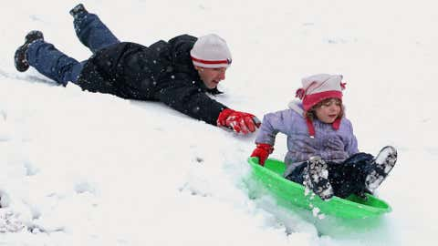 Chris Myers Asch gives his daughter Miriam Asch, 5, a little push down a hill at Takoma Park Middle School as a wet and heavy snow falls during Winter Storm Virgil on March 25, 2013 in Takoma Park, Maryland. (Chip Somodevilla/Getty Images)
