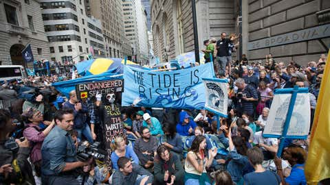 Demonstrators stage a sit-in on Broadway during a march protesting for action on climate change and Wall Street greed, Monday, Sept. 22, 2014, a day after a huge climate march in New York City. (AP Photo/John Minchillo)