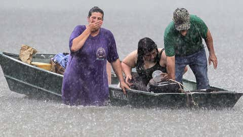 Dee Vazquez, from left, helps Georgette Centelo and her grandfather Lawrence Roberts after they tried to recover their belongings from a family mobile home in Central, north of Baton Rouge, Lousiana, Monday, Aug. 15, 2016.