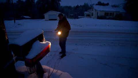 Jim Ridley uses a flashlight to get his mail Thursday, Dec. 26, 2013, in Litchfield, Maine, where he has been without electricity since Monday's ice storm. (AP Photo/Robert F. Bukaty)