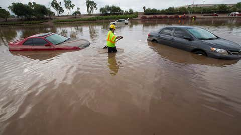 Arizona Department of Transportation (ADOT) worker Carlos Parra looks for drains to clear flood waters on I-10 east at 43rd Ave. after monsoon rains flooded the freeway in Phoenix, Monday, Sept. 8, 2014. (AP Photo/The Arizona Republic, Michael Chow)