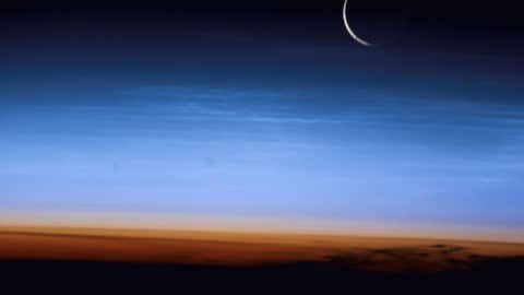 This image illustrates where the troposphere ends abruptly at the tropopause, which appears in the image as the sharp boundary between the orange- and blue- colored atmosphere. The silvery-blue noctilucent clouds extend far above the Earth's troposphere. (NASA/Getty Images)