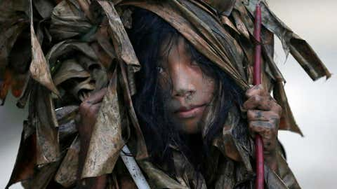 A muddied girl, donning a cape made of dried banana leaves, collects candles before attending a mass to celebrate the Feast Day of St. John the Baptist in the village of Bibiclat, Aliaga township, Nueva Ecija province in northern Philippines, June 24, 2015. (AP Photo/Bullit Marquez)