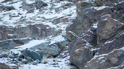A snow leopard is seen camouflaged against a mountain near the Indian Himalayas on Feb. 18, 2014. (David 'Baz' Jenkins/Caters News Agency)