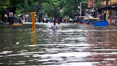 A boy wades through a flooded street in Chennai, in the southern Indian state of Tamil Nadu, Wednesday, Dec. 2, 2015. Weeks of torrential rains have forced the airport in the state capital Chennai to close and have cut off several roads and highways, leaving tens of thousands of people stranded in their homes, government officials said Wednesday. (AP Photo)