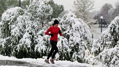 Heavy snow weighs down trees and bushes as a woman runs in Washington Park in Denver on Monday, May 12, 2014. (AP Photo/Ed Andrieski)