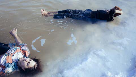 Women swim in a shallow pond that is a remnant of Lake Urmia. They walk almost two miles from the former beach to the pond several times each summer to bathe in the natural salt water. (Solmaz Daryani)