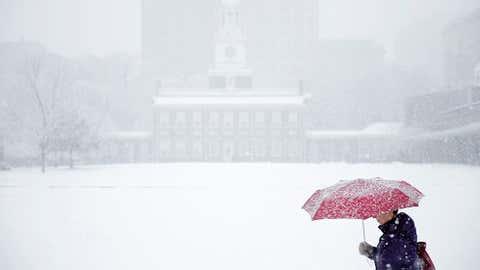 A woman walks past Independence Hall during a winter snowstorm, Dec. 10, 2013, in Philadelphia. (AP Photo/Matt Rourke)