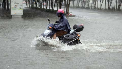 A motorcyclist rides through a flooded area in Jinjiang, south China's Fujian province of July 23, 2014 as typhoon Matmo makes landfall in China. (AFP/Getty Images)