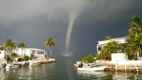 A waterspout forms behind some waterfront homes in Cudjoe Key, Fla. (movinondp/weather.com)