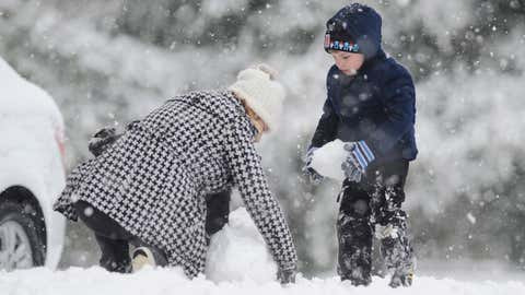 Angela Coxhead, left, and her 5-year-old son Liam Coxhead build a snowman outside a hotel, Wednesday, Feb. 25, 2015, in Attalla, Ala. Forecasters said the area was expected to receive some of the heaviest snow from a winter storm moving across the state and travel problems could persist into Thursday. (AP Photo/Jay Reeves)