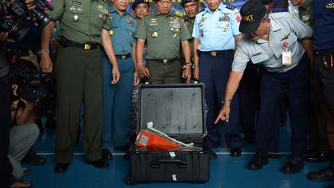 Tatang Kurniadi (R) from The National Transportation Safety Committee (KNKT) gestures next to Indonesian Military Chief General Moeldoko as Indonesian officers look at the FDR (Flight Data Recorder) of the AirAsia flight QZ8501 in Pangkalan Bun after it was retrieved from the Java Sea on January 12, 2015. (ADEK BERRY/AFP/Getty Images)