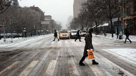 Pedestrians navigate the snow, ice and puddles along a Manhattan street on Feb. 2, 2015 in New York City. (Spencer Platt/Getty Images)
