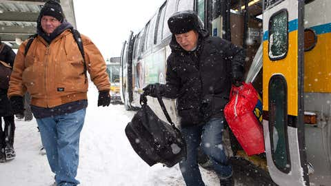 Commuters exit shuttle buses at the Massachusetts Bay Transportation Authority (MBTA) JFK/UMass stop on Monday, Feb. 9, 2015, in Boston, Massachusetts. The Red Line experienced substantial delays due to snow accumulation and two disabled trains Monday morning.  (Kayana Szymczak/Getty Images)