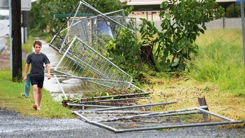 A boy walks past a fence brought down by Tropical Cyclone Marcia along the road into the northern Queensland town of Yeppoon on February 20, 2015. (PETER PARKS/AFP/Getty Images)