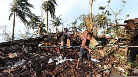 Samuel (L) and his father Phillip search through the ruins of their family home on March 16, 2015 in Port Vila, Vanuatu. (Dave Hunt-Pool/Getty Images)