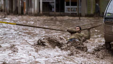 A man clings to a security line to cross a street flooded by the overflowing of the Copiapo River due to heavy rainfall that affected some areas in the city, in Copiapo, Chile on March 26, 2015. (STR/AFP/Getty Images)