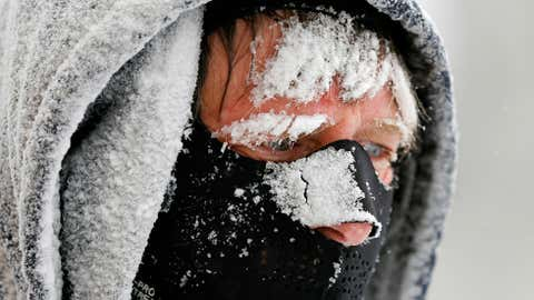Bob Landon blows snow from a sidewalk in the South End neighborhood on Thursday, March 13, 2014, in Albany, N.Y. Bitter cold temperatures return after a winter storm dumped up to six inches of snow and ice on the Capital Region. (AP Photo/Mike Groll)
