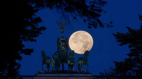 The perigee full moon, or supermoon, appears red behind the quadriga of the Brandenburg Gate in Berlin, Germany, Monday morning, Sept. 28,  2015. (Kay Nietfeld/dpa via AP)