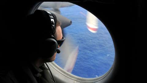In this photo taken from the Royal New Zealand Air Force P-3K2-Orion aircraft, a spotter looks out of a window in search of debris from the missing Malaysia Airlines Flight 370, in the Indian Ocean off the coast of western Australia on Sunday, April 13, 2014. (AP Photo/Greg Wood, Pool)