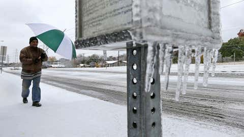 Joseph Mezo uses an umbrella as he walks to work in light sleet and icey conditions Friday morning, Dec. 6, 2013, in Dallas. (AP Photo/LM Otero)