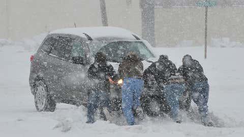 Good Samaritans help push a stranded motorist stuck in deep snow on Stefko Boulevard Thursday, Feb. 13, 2014 in Bethlehem, Pa.  (AP Photo/Chris Post)