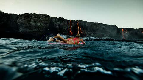 Professional adventurer Alison Teal has become the first woman to paddle out into lava during a volcanic eruption into the sea. Amazing shots of the extreme surf session shows the daredevil riding her pink surfboard up to the base of Kilauea Volcano on Hawaii's Big Island. (Perrin James/Caters News Agency)