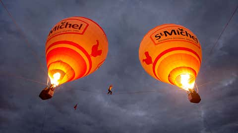 Tancrede Melet walks between two hot air balloons in southern France.