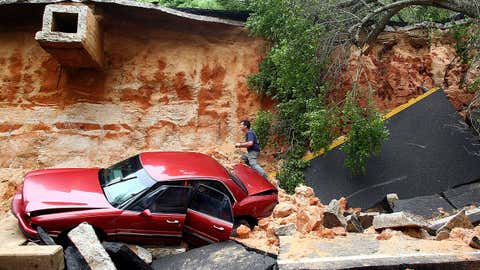 People survey the damage on Scenic Highway after part of the highway collapsed following heavy rains and flash flooding on April 30, 2014 in Pensacola, Florida. (Marianna Massey/Getty Images)