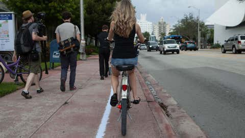 A woman rides a bike along the chalk outline showing how far inland 3 feet of sea level rise would reach in Miami Beach, Fla. (Courtesy Jayme Gershen/High Water Line)
