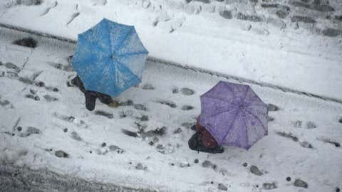 People hold umbrellas as they walk on the street covered with snow in Tokyo on February 8, 2014. Heavy snow struck Tokyo and other areas across Japan, grounding flights and suspending some train services (Toru Yamaka/AFP/Getty Images)