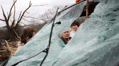 Michelle Boatright inspects the damage to a pickup truck the morning after a tornado ripped through the town February 6, 2008 in Atkins, Arkansas. (Photo by Rick Gershon/Getty Images)