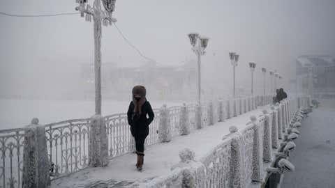 A woman walks over an ice-encrusted bridge in Yakutsk. Oymyakon lies a two day drive from the city of Yakutsk, the regional capital. (Amos Chapple)