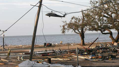 A U.S. military helicopter flies over destruction along Highway 90 in Biloxi, Mississippi, on August 30, 2005 after Hurricane Katrina hit the Gulf Coast. (NICHOLAS KAMM/AFP/Getty Images)