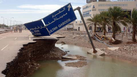 A road sign lies fallen at the side of a road that has slid away following a devastating tropical cyclone in the Omani capital Muscat on June 7, 2007. (MOHAMMED MAHJOUB/AFP/Getty Images)