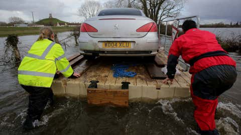 Volunteers use a pontoon to move a car that has been cut off by floodwaters at Burrowbridge on the Somerset Levels on February 27, 2014 in Somerset, England. (Matt Cardy/Getty Images)