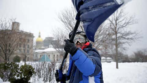 Marco Garcia, of Guatemala, shovels snow near the Statehouse in Tuesday, Feb. 18, 2014, in Trenton, N.J., after a quick-moving storm brought several inches of snow as well as rare 'thundersnow' to parts of the winter-weary East Coast. (AP Photo/Mel Evans)